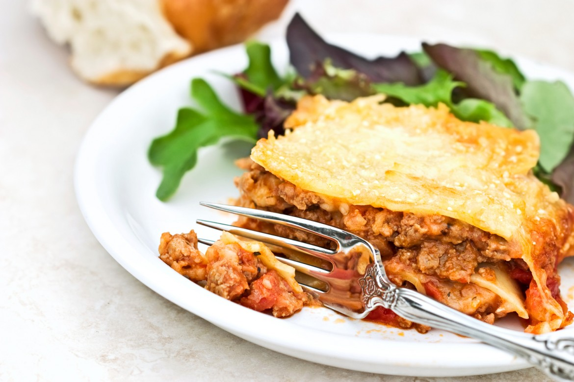 Fork cutting into meat lasagna with herb and mint salad and bread. Shallow DOF with focus on lasagna.